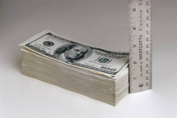 measuring a stack of dollar bills with a ruler